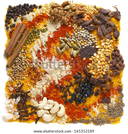 A huge range of indian spices and other ingredients, including black cardamom, chilli, black chickpeas, cashew nuts and walnuts, black (soy) beans, cloves, fenugreek powder, mustard seeds, etc - stock photo