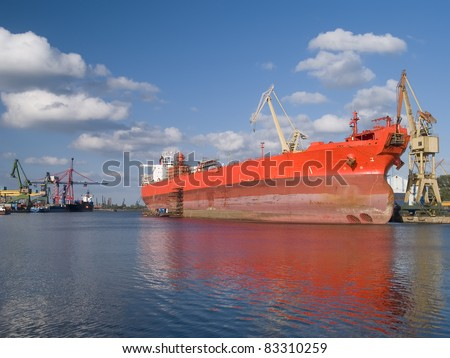 A huge red ship during hull repair - stock photo