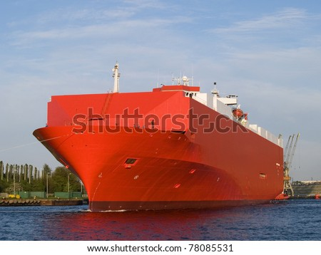 A huge red ship on its way to a new port of call - stock photo