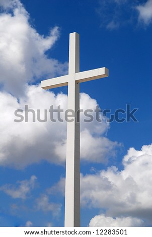 A huge religious cross on a beautiful partly cloudy blue sky - stock photo