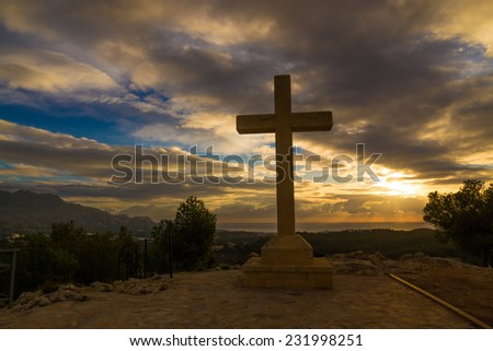 A huge stone cross against a dramatic sky - stock photo