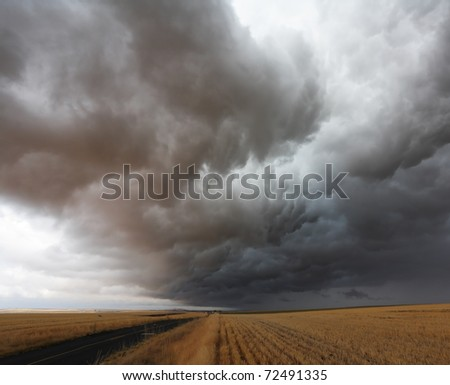 A huge storm cloud over the field after harvest in Montana - stock photo