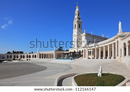 A huge tower and a marble colonnade around the square. The grand memorial and religious complex in the small Portuguese town of Fatima.