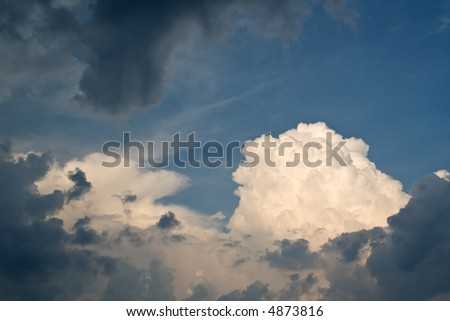 a huge white puffy cloud breaks through brooding gray ones - stock photo