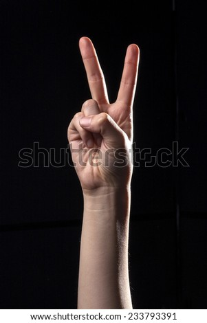 A human hand(finger) make the victory and means two in the china, er, chinese hand language isolated black at the studio.  - stock photo