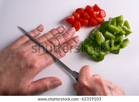 A human hand is being chopped with a knife on a cutting board. - stock photo