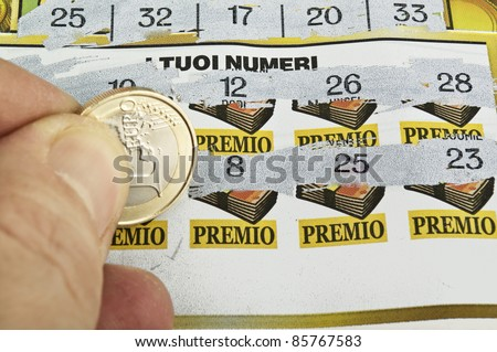 a  human hand is scratching a lottery ticket - stock photo