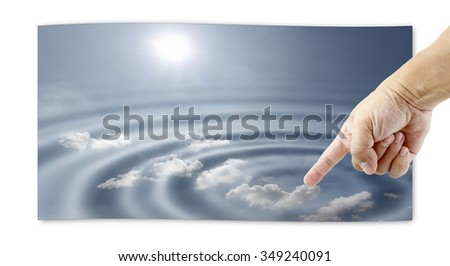 A human hand touching an picture of a surreal sky causing a circular ripple, for the concept of mankind interference with nature.  - stock photo