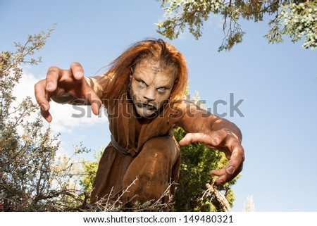 A human Lion creature reaches out menacingly to grab you.  Looking into the camera.  Character created by renowned special fx make-up artist Rayce Bird. - stock photo