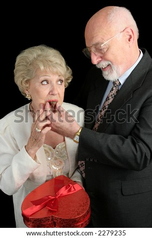 A humorous picture of a husband feeding his wife Valentine candy.  She doesn't look too sure about it.  Black background - stock photo