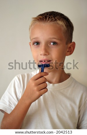 A humorous shot of a young boy shaving and looking at the camera