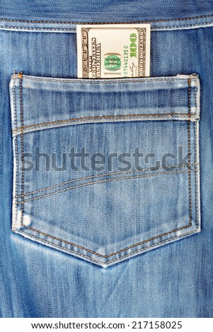 A hundred dollar bills sticking in the back pocket of denim blue jeans - stock photo