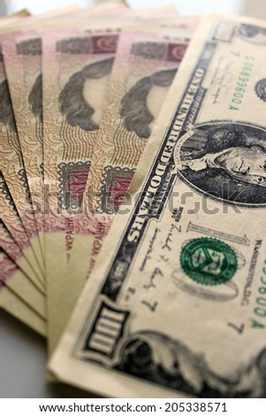 a hundred dollars laying on the Ukrainian grivnas banknotes - stock photo
