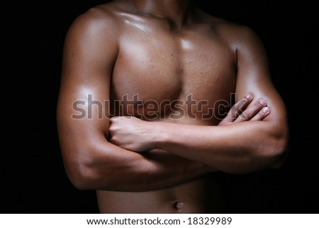 A hunky young asian male folding his hands with muscular chest - stock photo