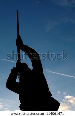 A hunter aiming his gun at a bird