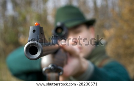 A hunter aiming whit a rifle. - stock photo
