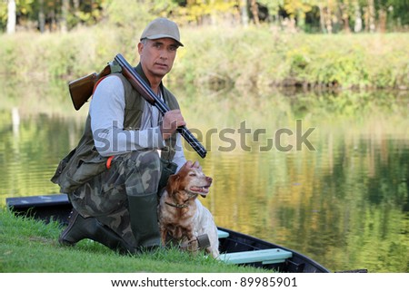 A hunter and his dog by a river. - stock photo