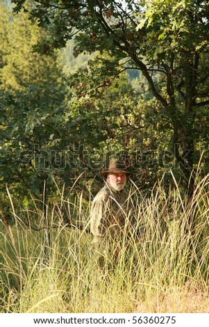 a hunter hides in the woods looking to find and shoot a Sasquatch Monster - stock photo