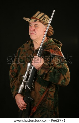 a hunter poses with his trusty rifle against a black background - stock photo