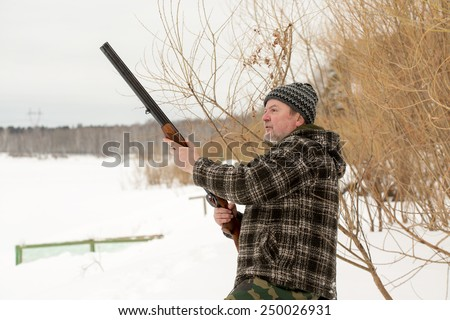 A hunter shooting a rifle in winter snowy landscape - stock photo