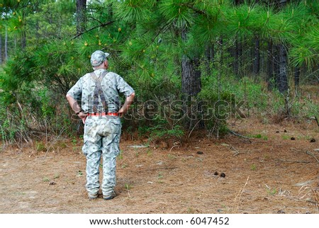 A hunter taking a look through the forest. - stock photo