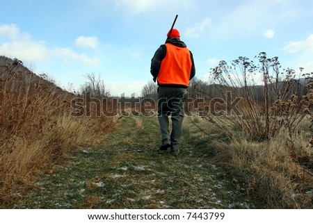 A hunter walking with gun in field - stock photo