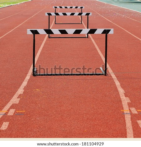 a hurdles on red running tracks - stock photo