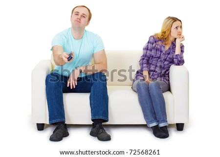 A husband and wife in a quarrel sit on the couch watching TV isolated on white background - stock photo