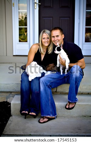 A husband, wife sit in front of their home with their white cat and French bulldog puppy. - stock photo