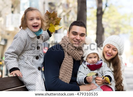 A husband with his beautiful caucasian wife and two children under five smiling and sitting on a bench outside. Shallow focus. Focused on a man.