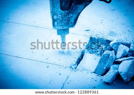a hydraulic arm with impact breaker at work,broken cement pavement - stock photo