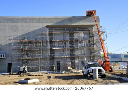 A hydraulic crane is used to lift construction material to roof of new building - stock photo
