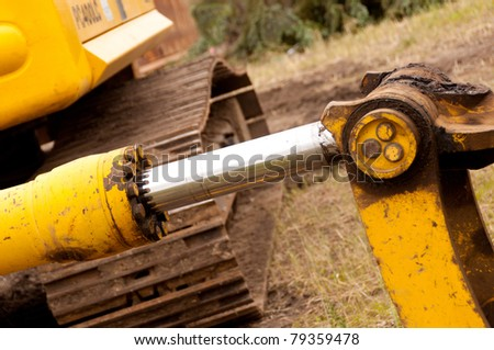 A Hydraulic Cylinder Painted Yellow with a Chrome Rod