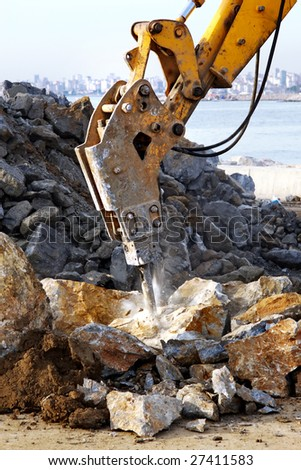 A hydraulic digger breaking up rock - stock photo