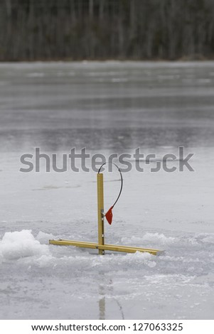 A ice fisherman's trap is set and ready to catch fish on a pond in northern Maine - stock photo