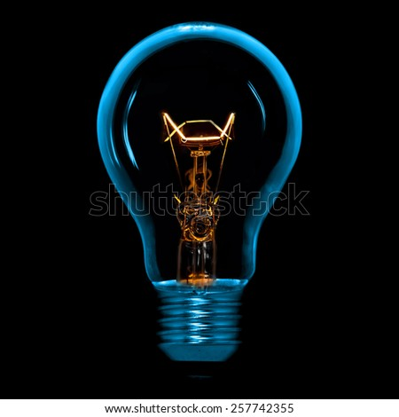 A incandescent light bulb isolated on black background
