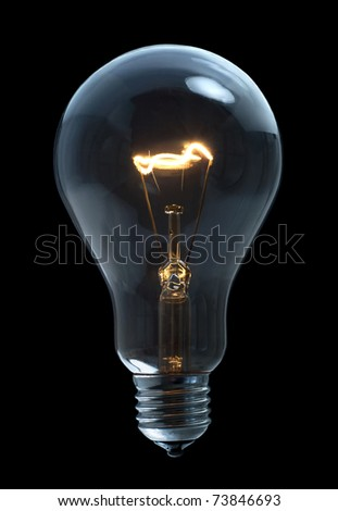 A incandescent light bulb on black background - stock photo