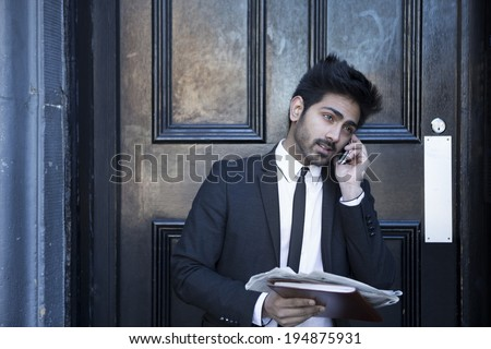 A Indian man in a business suit takes a phone call while holding a newspaper. Urban man standing outside a black door. - stock photo