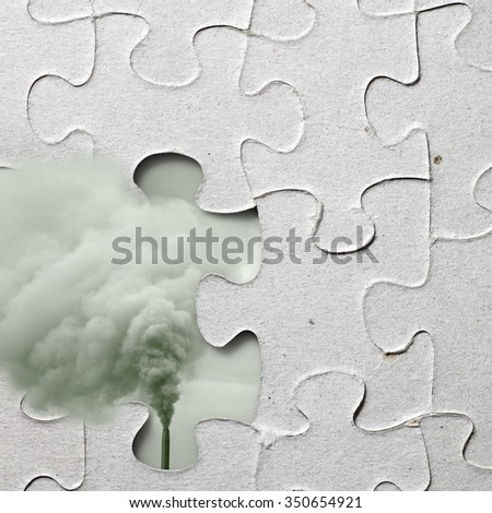 A industrial chimney spewing pollution exposed through a jigsaw puzzle with a missing piece for the concept of conundrum of industrial pollution. - stock photo