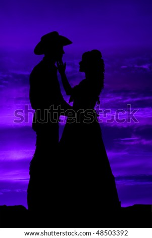 A intense moment for a cowboy and his gal, they are looking into eachothers eyes while she gently touches his face with her fingers, while the sky changes it many colors. - stock photo