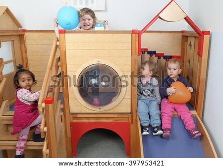A International Kindergarten with four kids playing on a slide - stock photo