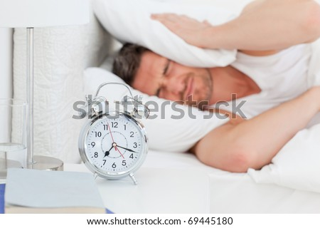A irritate man in his bed before waking up in his bedroom - stock photo