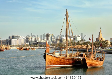 A jalibut dhow, with its distinctive vertical prow, tied up next to a smaller traditional boat - possibly a zaruq - in front of the landmark spiral mosque in Doha, Qatar - stock photo