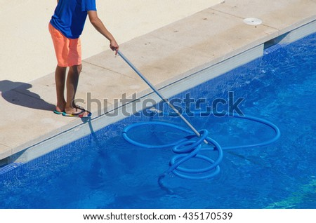 A janitor cleans the swimming poll. Summer work