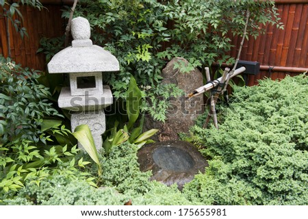 A Japanese garden scene featuring a water feature