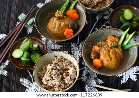 A japanese lunch for two: mixed grain rice, lightly pickled cucumber and shirataki and mochi kinchaku, a Japanese stuffed fried tofu beggar's purse garnished with carrot, shiitake mushroom and okra - stock photo