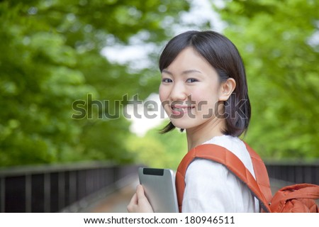 A Japanese student looking back while holding a tablet PC, - stock photo