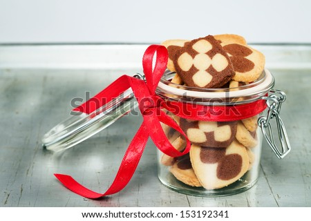 a jar filled with christmas cookies on a silver metal tray - stock photo