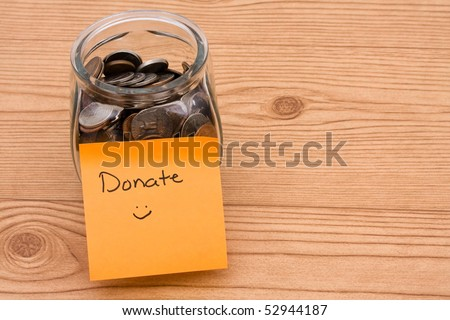 A jar full of change sitting on a wooden background, Please help by donating money - stock photo