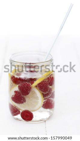 A jar full of cold drink with lemon and raspberries - stock photo
